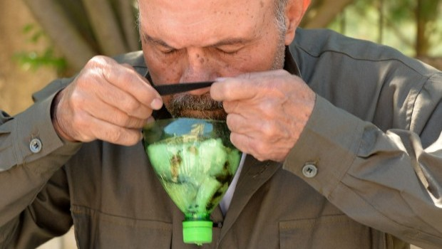 A picture taken on April 26, 2013 shows Abu Tarek, a 74-year-old retired army officer, trying on a homemade gas-mask assembled using a plastic bottle, coal, cotton, gauze, cola, and cardboard, for protection against chemical weapons, in Syria's northern Latakia province. (AFP PHOTO / MIGUEL MEDINA)
