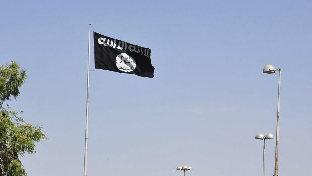 Vehicles drive past a flag of the al-Qaeda linked Islamic State of Iraq and the Levant, fluttering at the entrance to the city of Raqqa, eastern Syria, on October 4, 2013. (REUTERS/Nour Fourat)