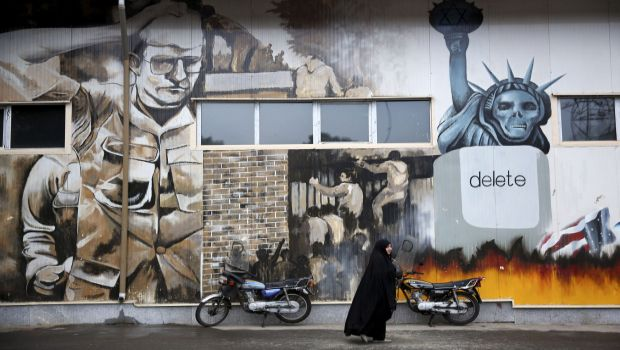 An unidentified woman walks under an anti-US graffiti painted on the walls of the former US Embassy in Tehran, Iran, on Saturday, November 2, 2013. (AP Photo/Ebrahim Noroozi)