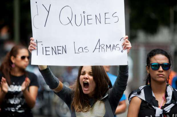 "A student from the Alejandro Humboldt University holds up a sign that reads in Spanish ""And who has the weapons?"" as she shouts slogans against Venezuela's President Nicolas Maduro to protest yesterday's killing of Bassil Da Costa, at the Alejandro Humboldt University where he studied in Caracas, Venezuela, Thursday, Feb. 13, 2014."