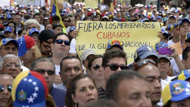 "An opposition activists shows a sign reading ""Cuban mercenaries out of the National Guard"" during a protest in front of the OAS headquarters building in Caracas on March 3, 2014. The latest wave of protests, which erupted on February 4 and up to now has left at least 18 people killed and 250 injured, has grown into the biggest threat to President Nicolas Maduro since he succeeded socialist icon Hugo Chavez last year. AFP PHOTO/JUAN BARRETO"
