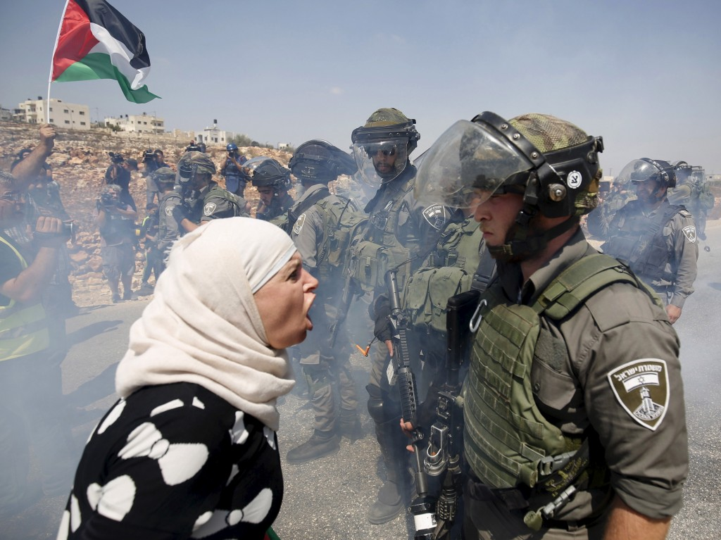A Palestinian woman argues with an Israeli border policeman during a protest against Jewish settlements in the West Bank village of Nabi Saleh, near Ramallah.