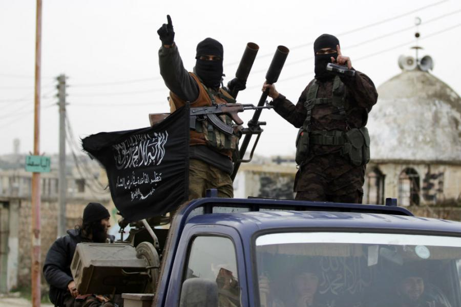 Members of al Qaeda's Nusra Front gesture as they drive in a convoy touring villages in the southern countryside of Idlib.