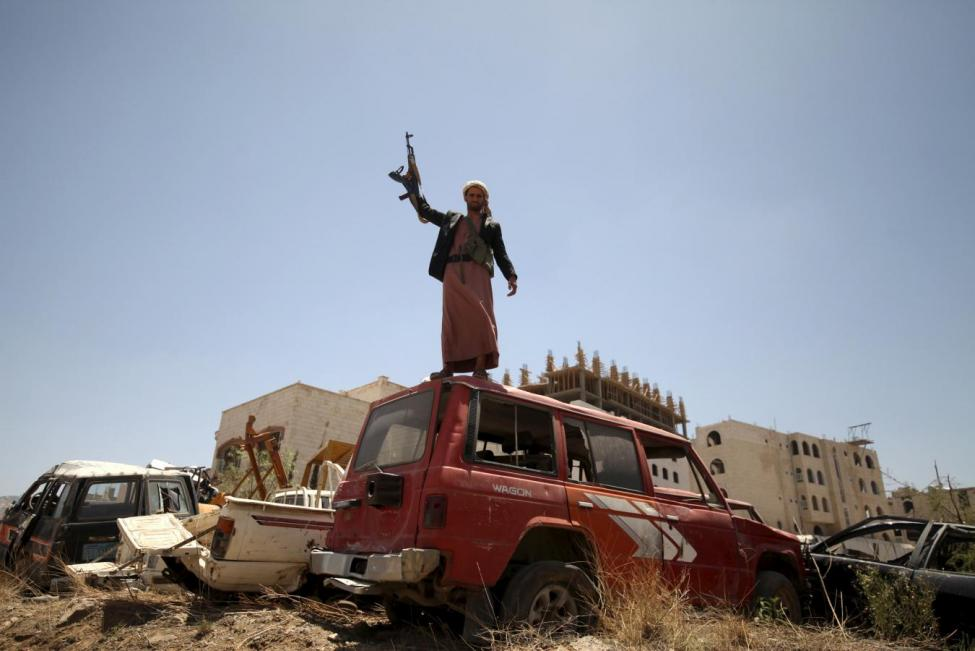 A follower of the Houthi group raises his weapon as he stands on a vehicle on a damaged street, caused by an April 20 air strike that hit a nearby army weapons depot, in Sanaa April 21, 2015. REUTERS/Mohamed al-Sayaghi
