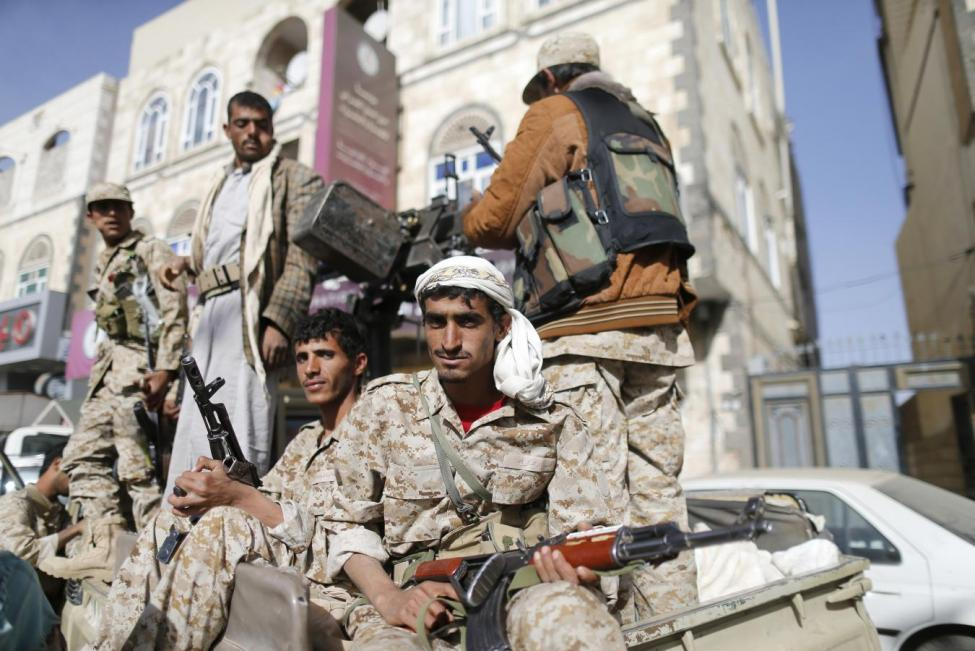 Houthi fighters ride a truck while patrolling a street in Sanaa