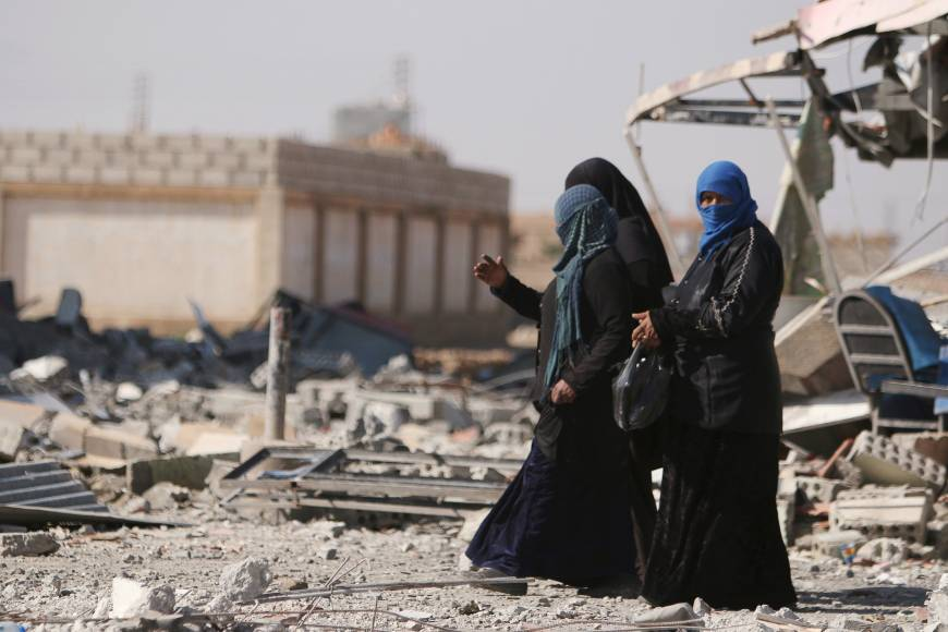 Women walk in the war-ravaged town of al-Shadadi in Hasaka province, northeast Syria, on Friday.
