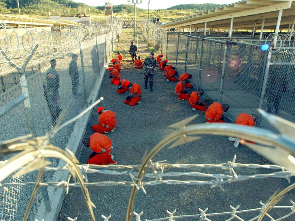 Military Police guard Taliban and al Qaeda detainees in orange jumpsuits. 11 January 2002 Getty