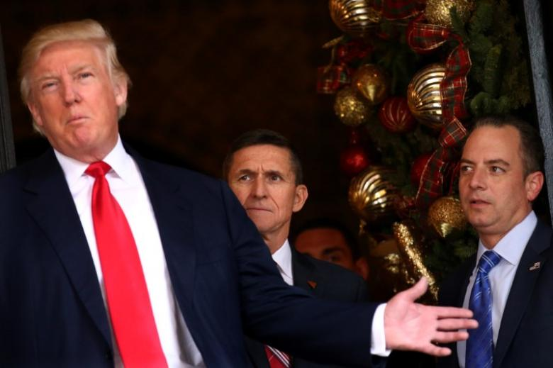 Incoming White House Chief of Staff Reince Priebus and U.S. Army Lieutenant General Michael Flynn look at U.S. President-elect Donald Trump as he talks with the media at Mar-a-Lago estate where Trump attends meetings, in Palm Beach, Florida