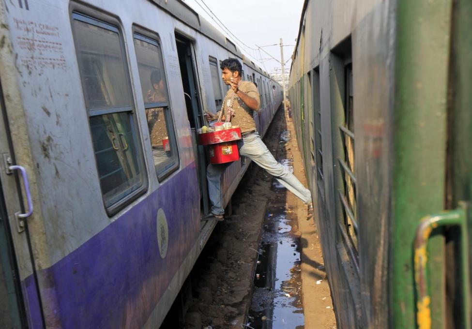 A vendor moves from one train to another at a railway station in Kolkata