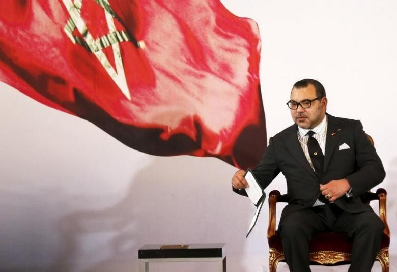 Morocco's King Mohammed VI holds a book during a visit, at the presidential palace in Abidjan