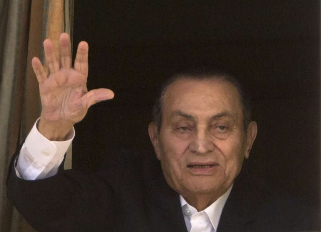 Ousted former Egyptian President Hosni Mubarak waves to his supporters last year from his hospital room in Cairo, Egypt