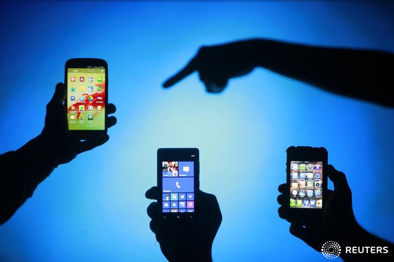 Men are silhouetted against a video screen as they pose with Samsung Galaxy S3, Nokia Lumia 820 and iPhone 4 smartphones (L-R) in this photo illustration taken in the central Bosnian town of Zenica, May 17, 2013. REUTERS/Dado Ruvic (BOSNIA AND HERZEGOVINA - Tags: BUSINESS TELECOMS) - RTXZQ6G