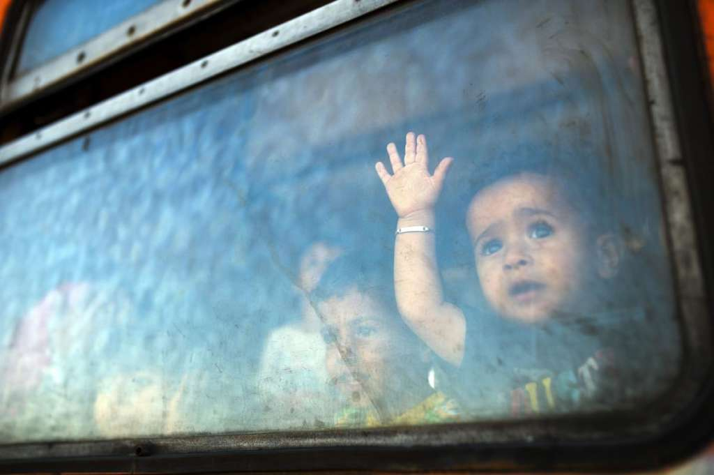 A migrant boy looks through a window onboard a train for Serbia at the new transit center for migrants at the border line between Greece and Macedonia near the town of Gevgelija on Aug. 28. (ROBERT ATANASOVSKI/AFP/Getty Images)