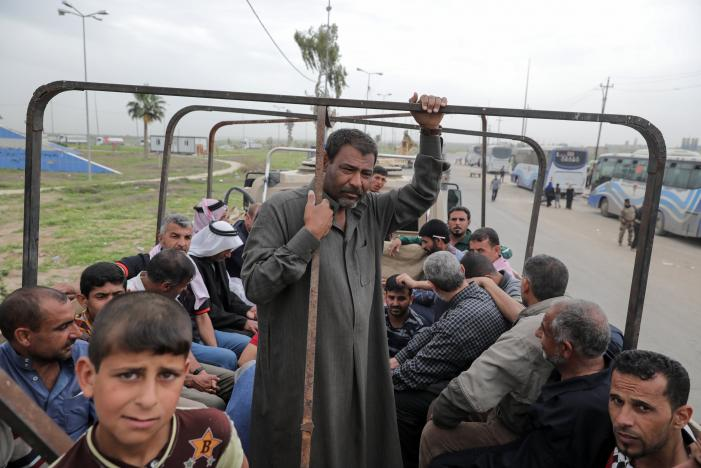 Displaced Iraqi men wait in a truck to be transported to a camp as the battle between the Iraqi Counter Terrorism Service and Islamic State militants continues nearby, in western Mosul