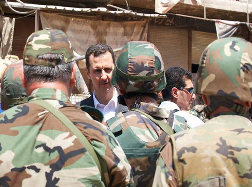 Syria's long-time despot Bashar al-Assad chats with military personnel during his visit to a military site in the town of Daraya, southwest of Damascus REUTERS/SANA/Handout via Reuters