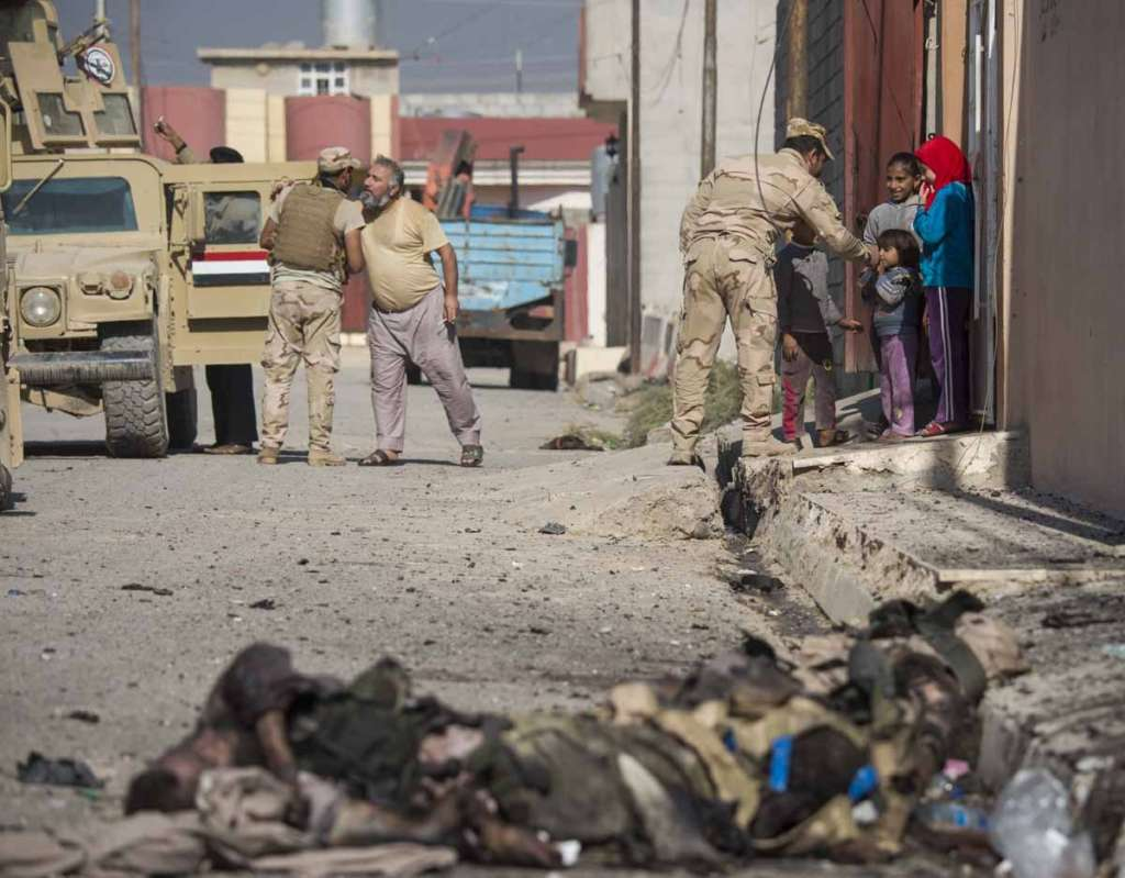 Bodies of ISIS fighters lie on a street in Mosul's eastern Al-Intissar neighborhood as Iraqi soldiers talk to residents.