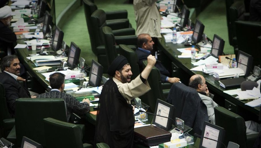 An Iranian Member of Parliament (MP) shakes his fist as he chants anti-Britain slogans during a debate in parliament