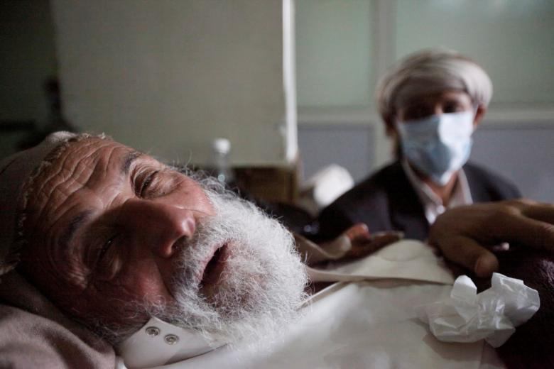 An old man infected with cholera lies on the bed at a hospital in Sanaa