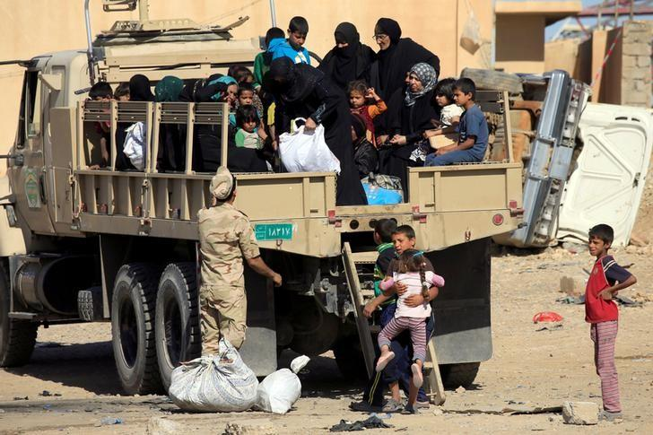 Displaced Iraqi people who fled from clashes ride in a military truck during a battle between Iraqi forces and Islamic state militants in western Mosul