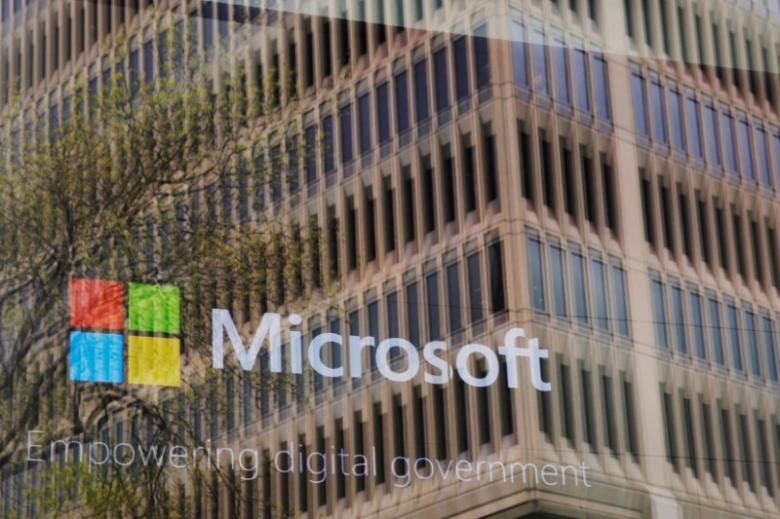 An advertisement plays behind a window reflecting a nearby building at the Microsoft office in Cambridge