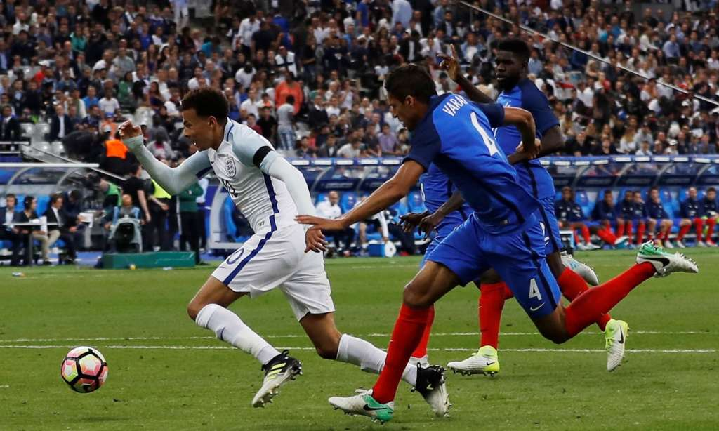 England's Dele Alli is fouled by France's Raphaël Varane early in the second half. After the referee consulted his video assistant, Varane was sent off.
