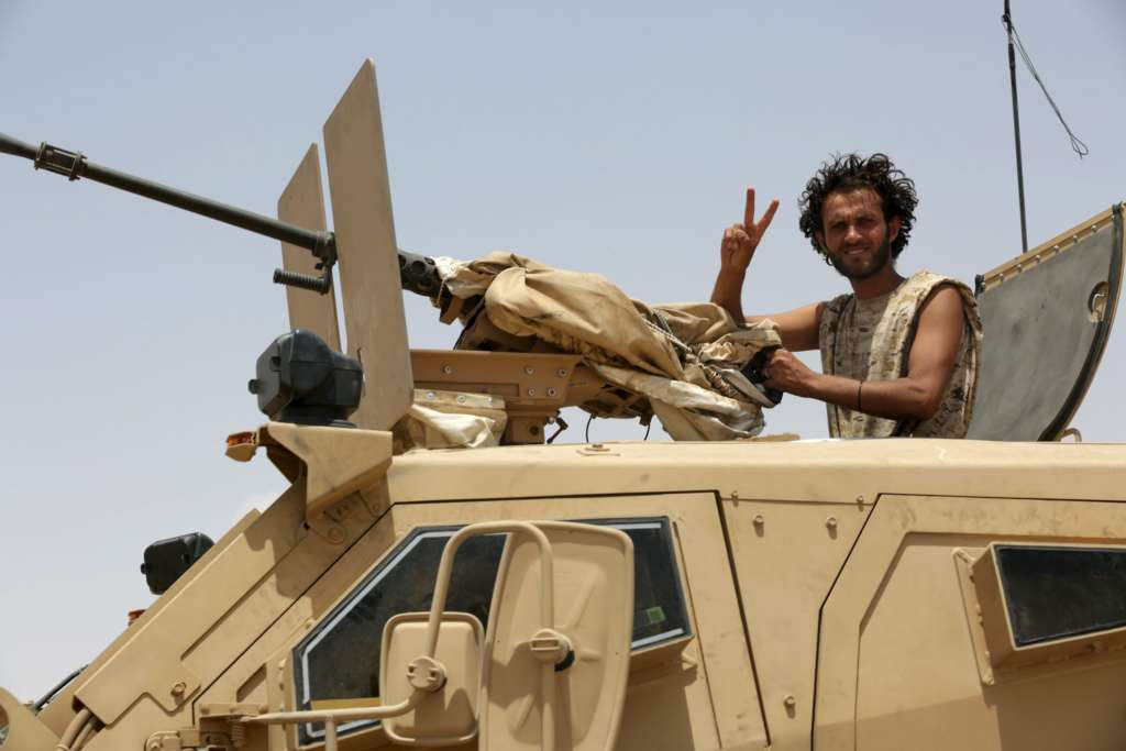 A soldier gestures as he sits atop a military vehicle accompanying Gulf Arab soldiers while they arrive at Yemen's northern province of Marib