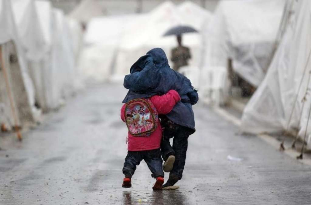 Syrian boys walk shoulder to shoulder in the rain at the Boynuyogun refugee camp on the Turkish-Syrian border in Hatay province.