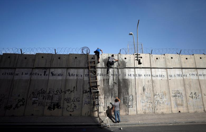 Palestinians climb over a section of the controversial Israeli barrier as they try to make their way to attend the second Friday prayers of Ramadan in Jerusalem's al-Aqsa mosque, near Ramallah
