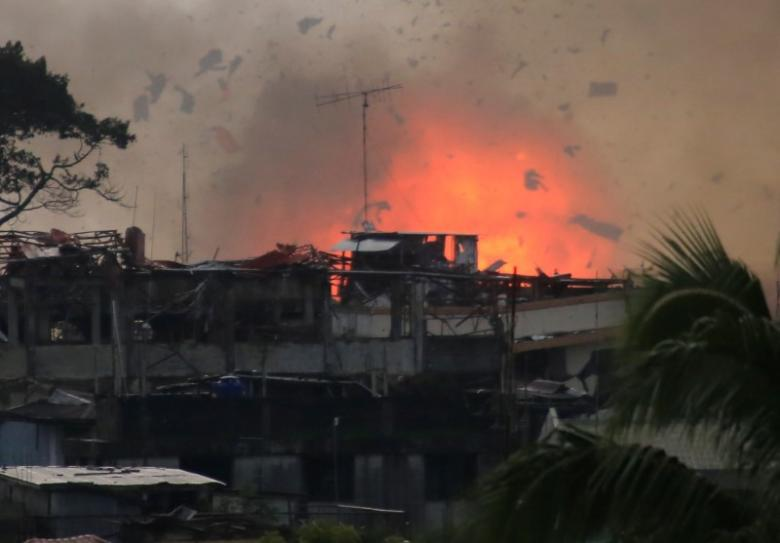 Debris and fire is seen after OV-10 aircraft released bomb during airstrike in Marawi