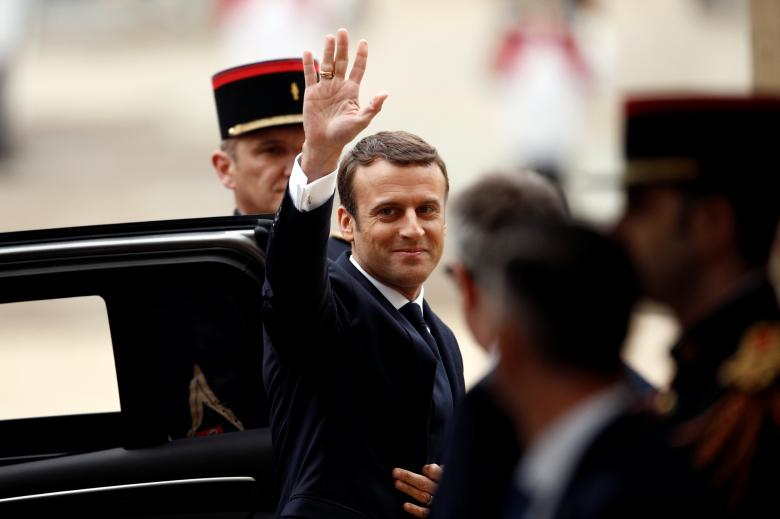 French President-elect Emmanuel Macron waves as he arrives to attend a handover ceremony with outgoing President Francois Hollande at the Elysee Palace in Paris