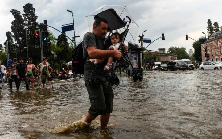 A pedestrian carries a child in a pushchair as he crosses a street after a heavy downpour of rain and hail at Besiktas near Istanbul on July 27, 2017