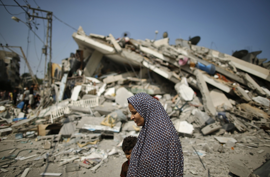 A Palestinian woman walks past the rubble of a residential building