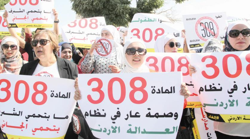 Protesters in front of Jordan's parliament in Amman hold banners calling for the repeal of a provision that allows a rapist to escape punishment if he marries his victim.