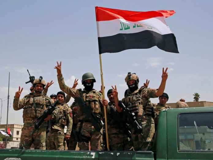 "Iraqi forces make a ""V"" sign and display an Iraqi flag as part of a victory celebration after defeating ISIS militants and retaking the Grand al-Nuri Mosque in the Old City in Mosul."