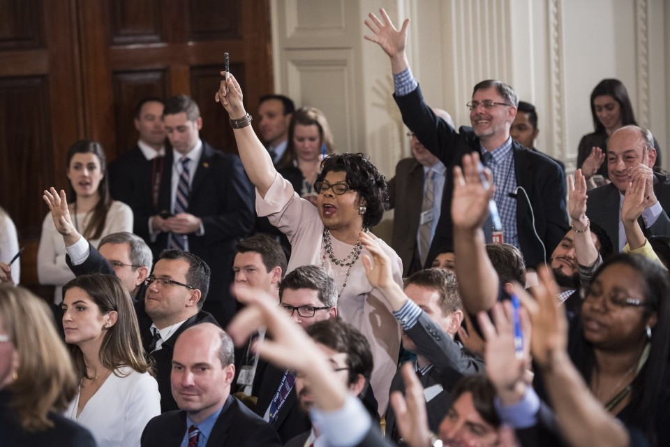Members of the media raise their hands for questions.
