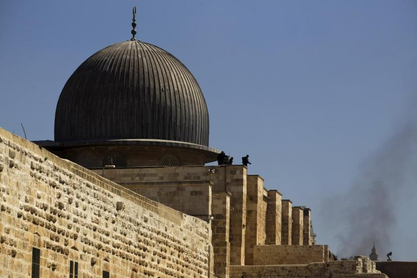 Israeli police officers take positions on the roof of Aqsa mosque during clashes with Palestinians in Jerusalem's Old City