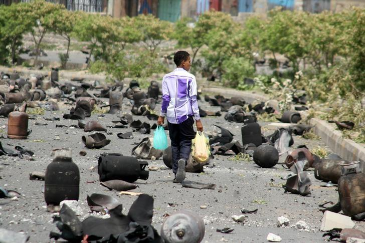 A boy walks on a street littered with cooking gas cylinders after a fire and explosions destroyed a nearby gas storage during clashes between fighters of the Popular Resistance Committees and Houthi fighters earlier today, in Taiz