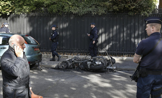 Police officers stand next to a burnt scooter outside the office of Jordan's military attache in Paris
