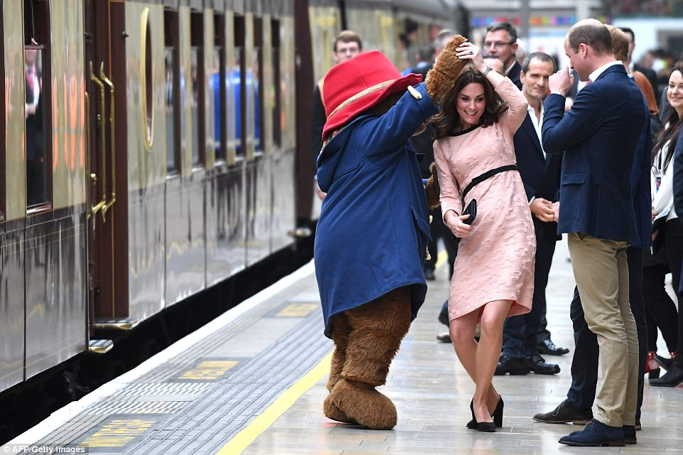 Kate Middleton dancing with the giant bear at Paddington station before a crowd of impressed onlookers.