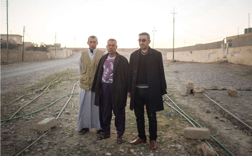 Three members of a Sunni tribal militia stand near a road on the outskirts of Muneira, Iraq. After ISIS fighters were driven out last fall, militiamen set fire to houses belonging to residents accused of sympathizing with the militants.