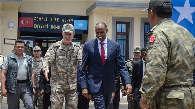 Turkish army's Chief of General Staff Hulusi Akar, center left, escorts Somali Prime Minister Hassan Ali Khayre during an inauguration ceremony of the Turkish military base in Mogadishu on September 30, 2017.