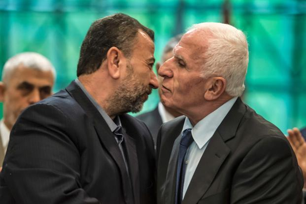 Fatah's Azam al-Ahmad (right) and Saleh al-Aruri of Hamas kiss after signing a reconciliation deal in Cairo on Thursday.